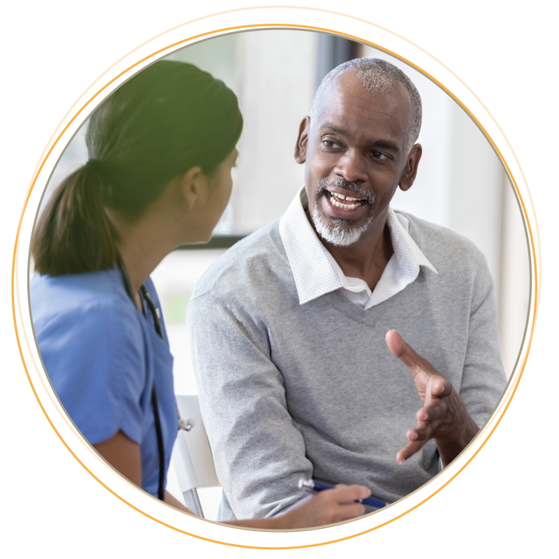 Black middle aged man talking with a nurse.